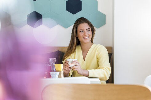 Smiling young woman in a cafe holding cup of coffee - DIGF03938