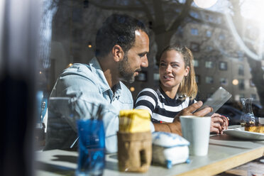 Young woman and man sharing tablet in a cafe - DIGF03944