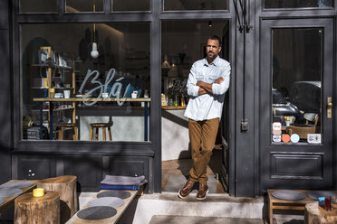 Man standing at entrance door of a cafe - DIGF03947