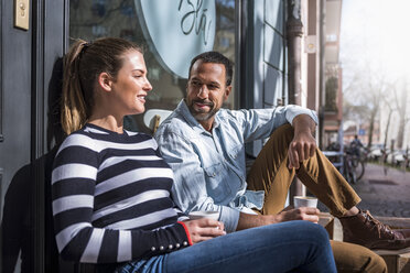 Man and woman sitting outside a cafe talking - DIGF03950