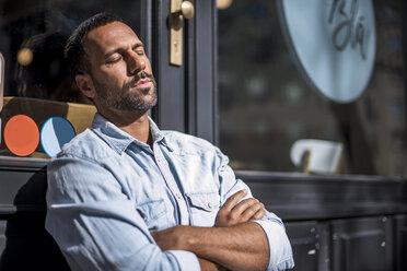 Relaxed man outside a cafe enjoying the sunshine - DIGF03953