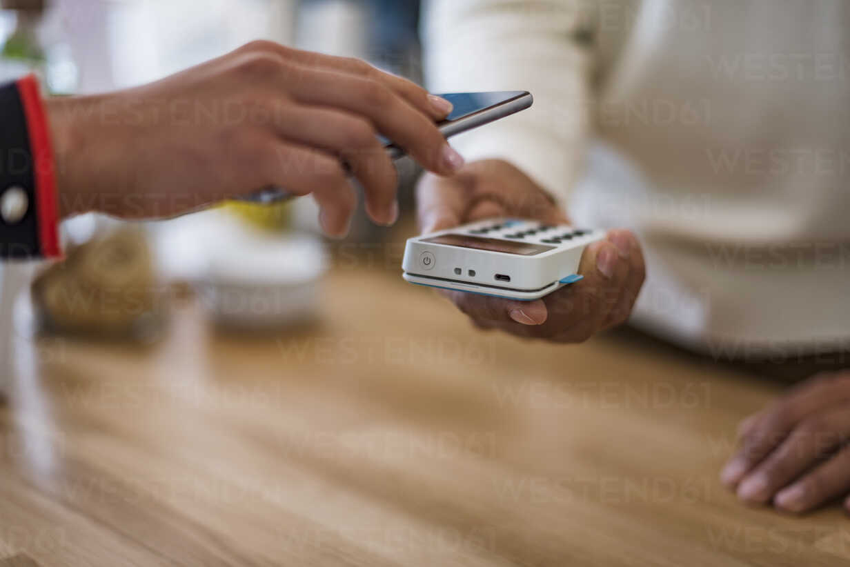 Close-up of customer paying cashless with smartphone at counter of a store - DIGF03959 - Daniel Ingold/Westend61