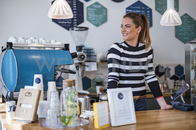 Smiling young woman behind the counter of a cafe - DIGF03962