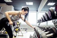 Woman exercising with dumbbells in gym - DAWF00615