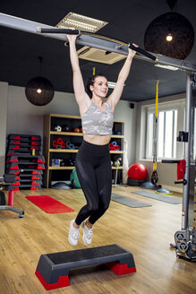 Woman doing a jumping exercise with bar in gym - DAWF00621