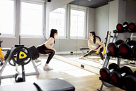 Woman exercising in gym looking in mirror - DAWF00624