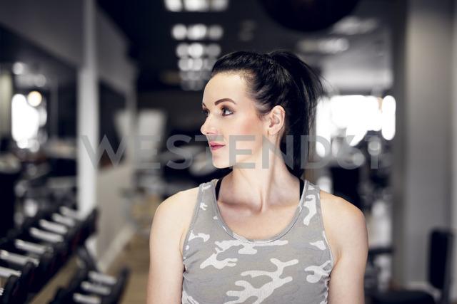 Sportive woman in gym looking sideways - DAWF00630