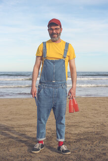 Portrait of smiling man in dungarees standing on the beach holding bottles of soft drinks - RTBF01174