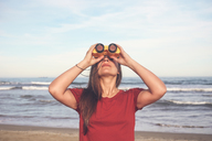 Woman using binoculars on the beach - RTBF01177