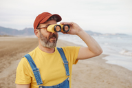 Bearded man using binoculars on the beach - RTBF01183