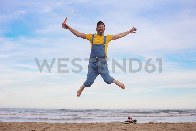 Portrait of happy man in dungarees jumping with soda in hand on the beach - RTBF01186