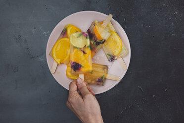 Hand taking homemade orange lemon popsicle with edible flowers from plate - SKCF00440
