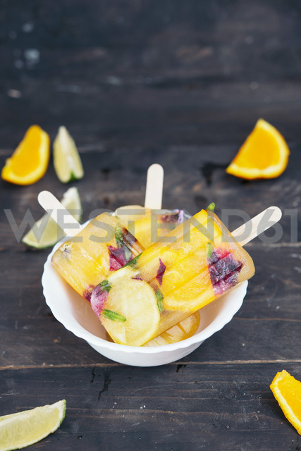 Bowl of homemade orange and lemon popsicles with edible flowers - SKCF00443