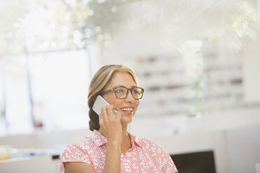 Smiling businesswoman talking on smart phone - HOXF03374