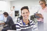 Portrait smiling, confident creative businesswoman with headphones - HOXF03380
