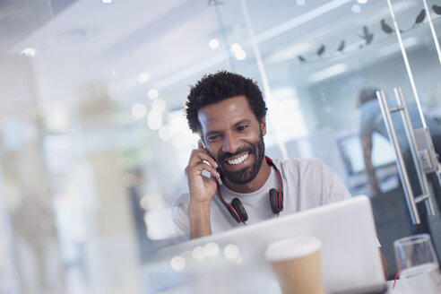 Smiling, confident creative businessman talking on smart phone at laptop in office - HOXF03419