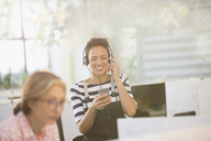 Smiling creative businesswoman listening to music with headphones and smart phone - HOXF03446