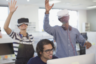 Computer programmers testing virtual reality simulators in office - HOXF03458