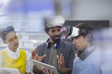 Computer programmers with digital tablet programming virtual reality simulators - HOXF03476