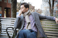 Thoughtful man looking away while relaxing on bench in park - CAVF45715