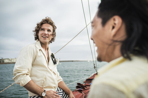 Happy man looking away while traveling with friend in sailboat - CAVF45742