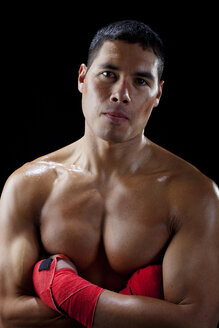 Portrait of shirtless confident boxer with arms crossed against black background - CAVF45814