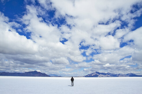 Rear view of man standing on snowy field against cloudy sky - CAVF45853