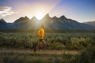 Side view of man running on field during sunset - CAVF45916