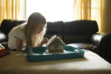 Girl decorating toy house while on sofa at home - CAVF45928
