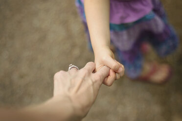 Cropped image of mother and daughter holding hands while walking on footpath - CAVF45934