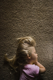 Overhead view of girl sleeping on rug at home - CAVF45937