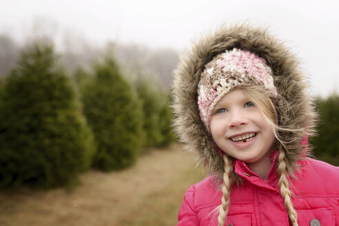 Cheerful girl looking away while standing in pine tree farm - CAVF45952