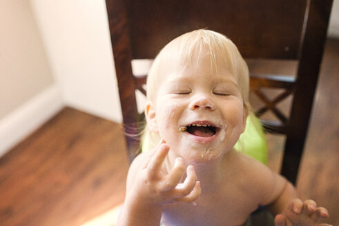 High angle view of happy boy with messy mouth sitting on chair - CAVF45964