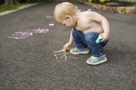 Shirtless boy writing with chalk on footpath - CAVF45979