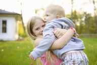 Portrait of happy girl carrying brother while standing in backyard - CAVF45997