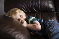 Cute boy looking away while relaxing on sofa at home - CAVF46018