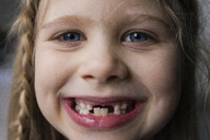 Close-up portrait of happy girl showing teeth - CAVF46033