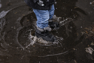 Low section of boy jumping in puddle on street - CAVF46042