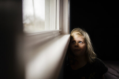Thoughtful girl looking through window while sitting at home - CAVF46048