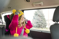 Happy girl wearing warm clothing traveling in car - CAVF46051