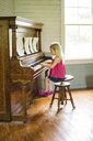 Side view of girl playing piano while sitting on stool at home - CAVF46054