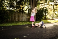 Girl looking at brother licking puddle on road - CAVF46072