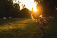 Happy girl dancing on grassy field during sunset - CAVF46087