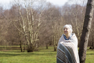 Thoughtful senior woman wrapped in blanket standing on field during winter - CAVF46147