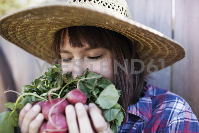 Young woman smelling radishes at organic farm - CAVF46204