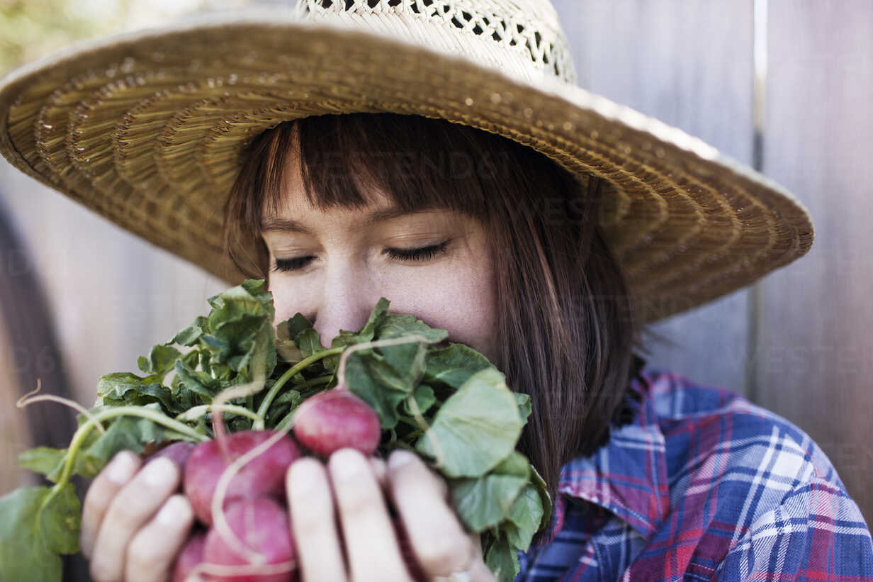 Young woman smelling radishes at organic farm - CAVF46204 - Cavan Images/Westend61