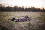 Full length of woman relaxing on grassy field - CAVF46219