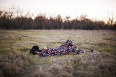 Full length of woman relaxing on grassy field - CAVF46219