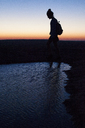 Silhouette woman walking by pond on field during sunset - CAVF46243