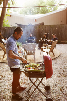 Man barbecuing while friends sitting in yard - CAVF46282